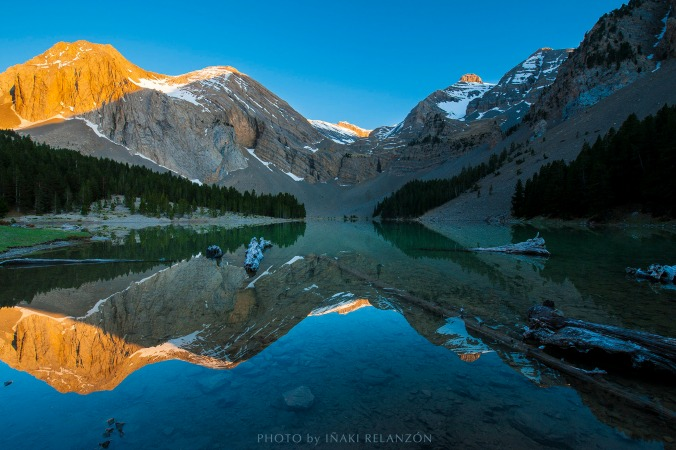 Stunning picture of a mountain tarn with reflections by iñaki Relanzón on nature photography holidays spain
