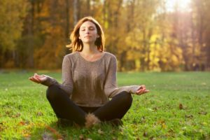A girl meditating outside on the grass on one of our meditation and yoga holidays