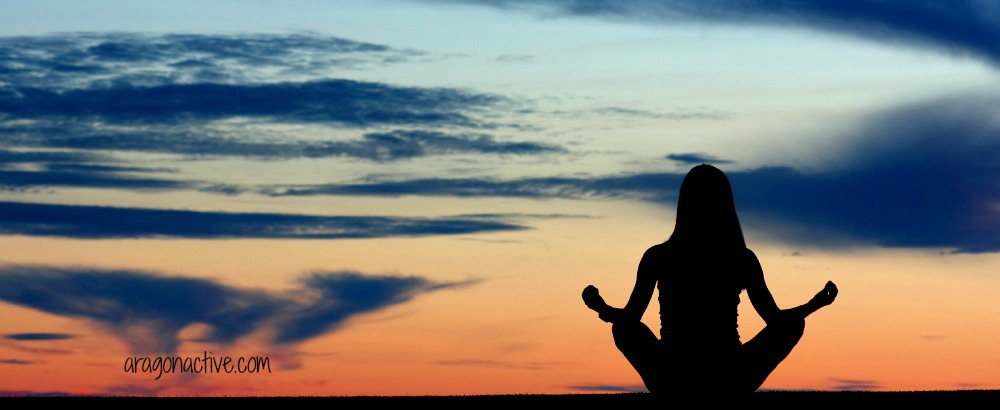 A girl meditating crossed legged at sunset on Importance of Meditation