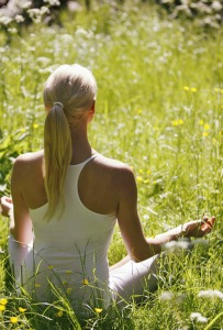 A girl meditating in a field on our Yoga Meditation Retreat Spain