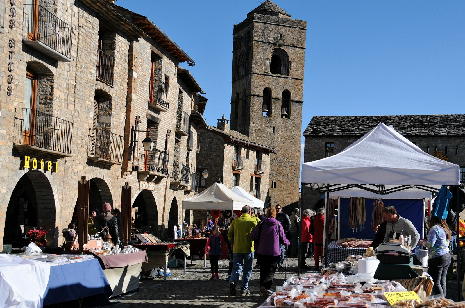 The square in the medieval town of Ainsa with foodstalls and people walking about on the Learn Spanish Holiday with Aragon Active