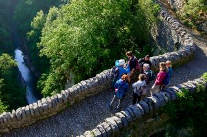 A small group of students on a bridge in the Ordesa National Park with a walking guide on the Aragon Active Learn Spanish Holiday