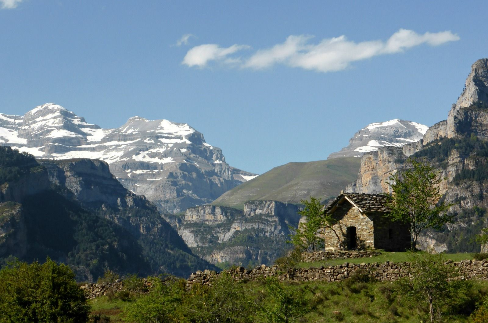 A stone barn perched on agreen terrace high in the Pyrenees with Monte Perdido behind in the Ordesa National Park on Aragon Active Self Guided Walking Holiday Spain