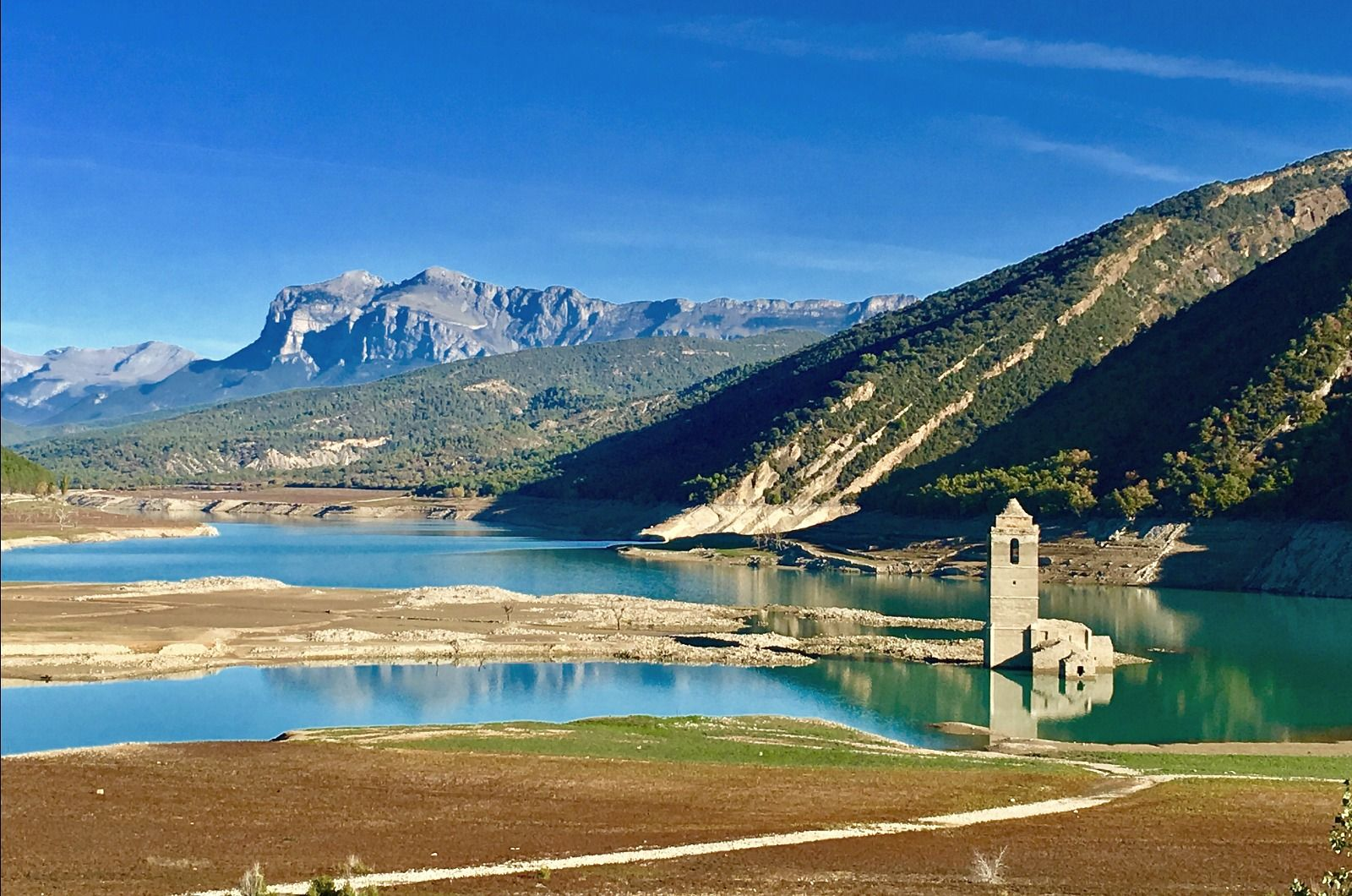 A view of the Mediano reservoir in the Pyrenees with the water low and the church visible on Aragon Active Tailor Made Activity Holiday Spain