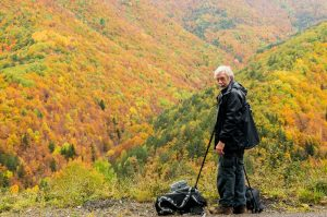 A photo of a photographer with tripod taking a photo of autumn in the Pyrenees on the Photography Holiday Spain with Aragon Active