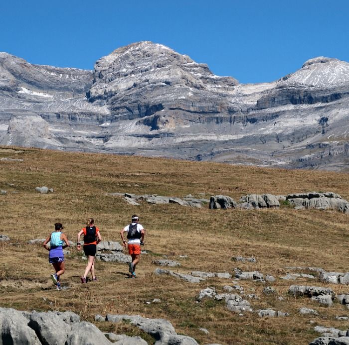 Three trail runners running uphill with the Pyrenees and Monte Perdido in the background on Aragon Active Trail Running Holiday