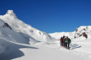 A group snowshoeing on the border with France in the Pyrenees on Snowshoeing Holidays Pyrenees with Aragon Active