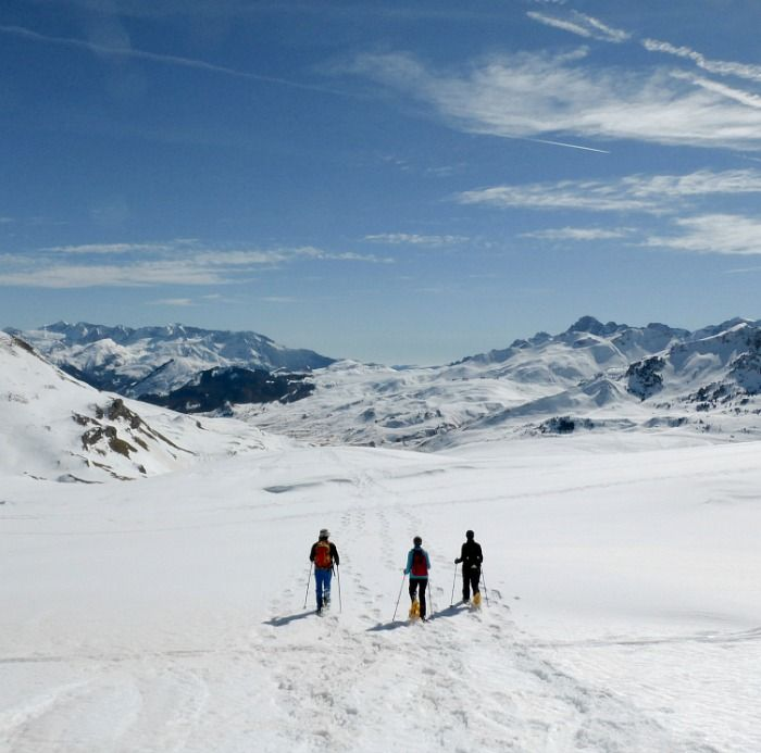 Snowshoeing down an open plain high in the Pyrenees on Aragon Active A group take a break at the summit of a mountain in the Pyrenees with Aragon Active Snowshoeing Holidays Pyrenees