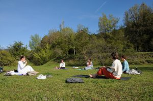 A group have a yoga class outdoors in the Pyrenees on the Yoga Meditation Retreat Spain with Aragon Active