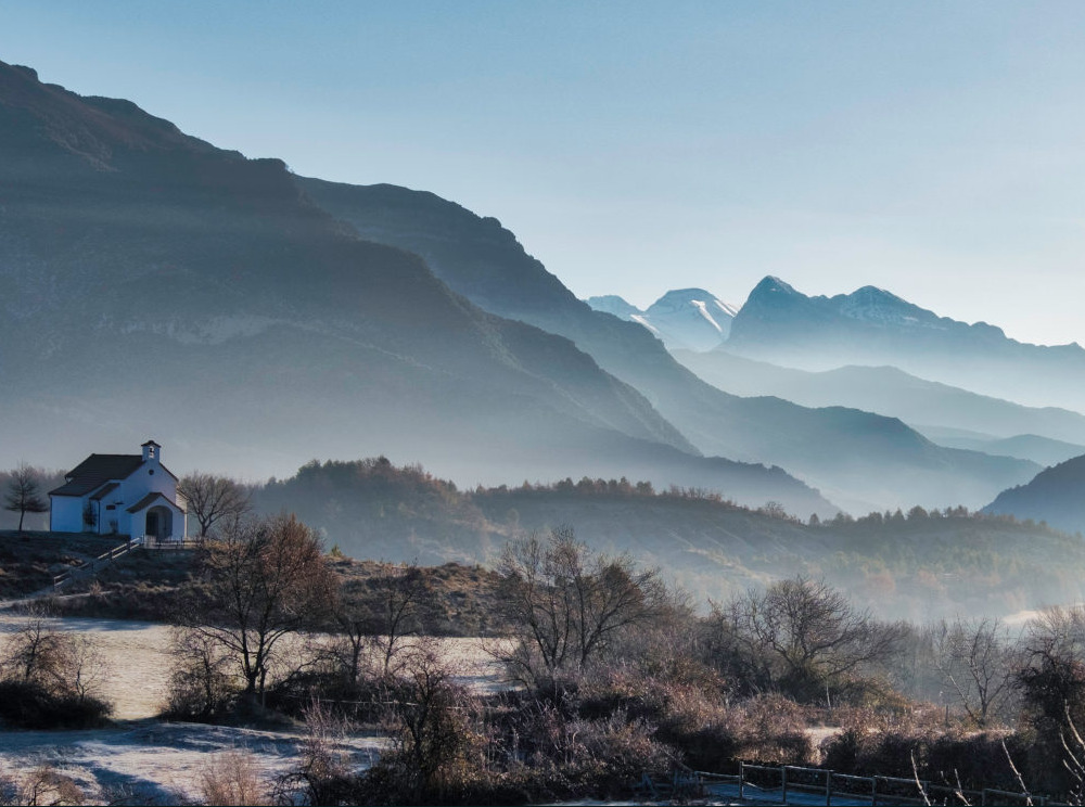 Frost on the ground and mist rising between the layers of mountains with the chapoel of San Urbez in the foreground on our Photography Holiday Spain