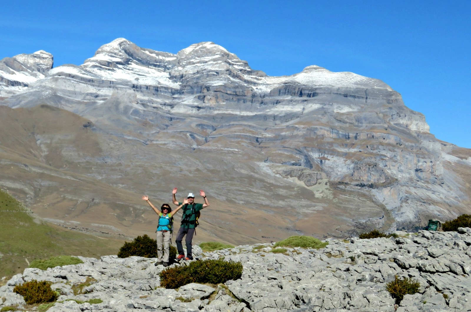 Two hikers waving on top of a ridge in the Spanish Pyrenees with Monte Pedido behind on our Guided Walking Holiday Spain