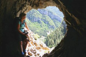 A view from the mouth of a cave with a hiker peering out on our Guided Walking Holiday Spain