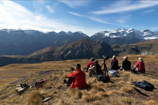 A group of photographers sit down to take in the panoramic view of the snow capped mountains of the Spanish Pyrenees at approximately 1700m altitude on our Photography Holiday Spain