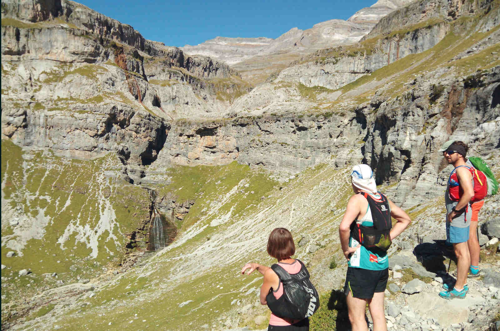 A group of trail runners pause to look at the horse tail falls from a high pathway in the Ordesa National Park in the Spanish Pyrenees on our Trail Running Holiday