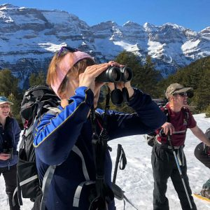 Anne looks through binoculars at a vulture on our Snowshoeing Holidays Pyrenees