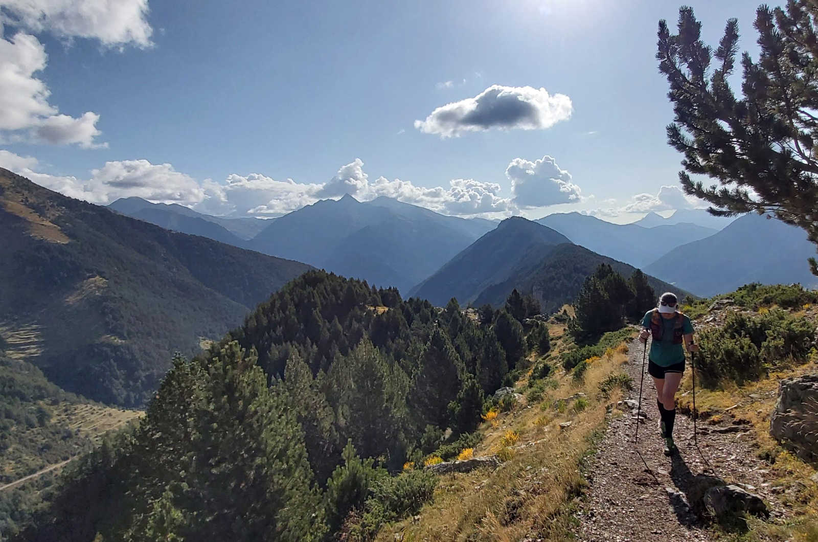 A female trail runner makes the ascent on a ridge in the Spanish Pyrenees with panoramic views on our Trail Running Holiday