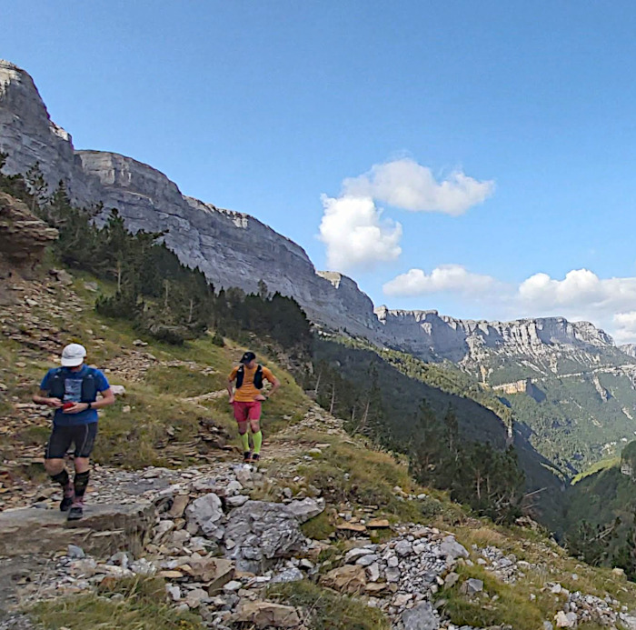 Two male trail runners on a faja (narrow pathway) in the Ordesa National Park in the Spanish Pyrenees on our Trail Running Holiday
