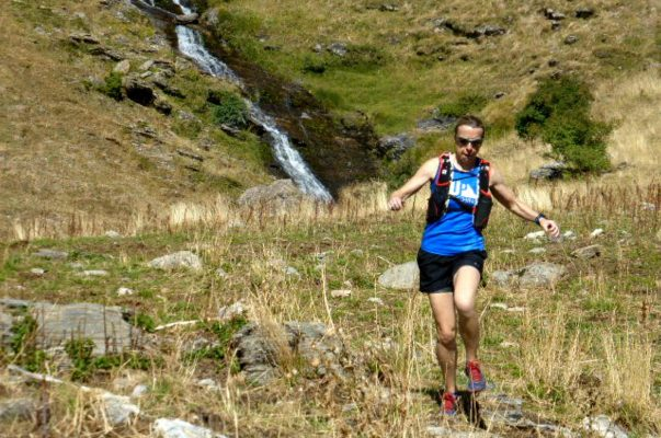 A female trail runner descends an open meadow with a waterfall behind in the Spanish Pyrenees on our Trail Running Holiday