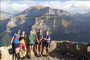 A group of five trail runners stop at a viewing balcony which overlooks the valley of Ordesa in the Spanish Pyrenees on our Trail Running Holiday