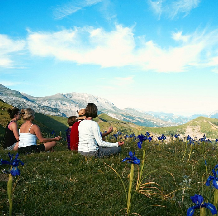 A group of yoga students take a minute to sit on top of a mountain surrounded by wild iris in the Spanish Pyrenees on our Yoga and Walking Retreat Spain