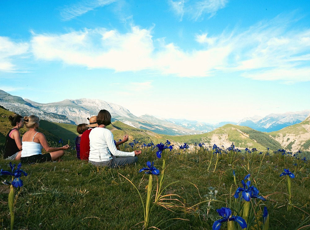 A group sit amongst blue wild iris in the Spanish Pyrenees for a moments meditation on our Yoga and Walking Retreat Spain
