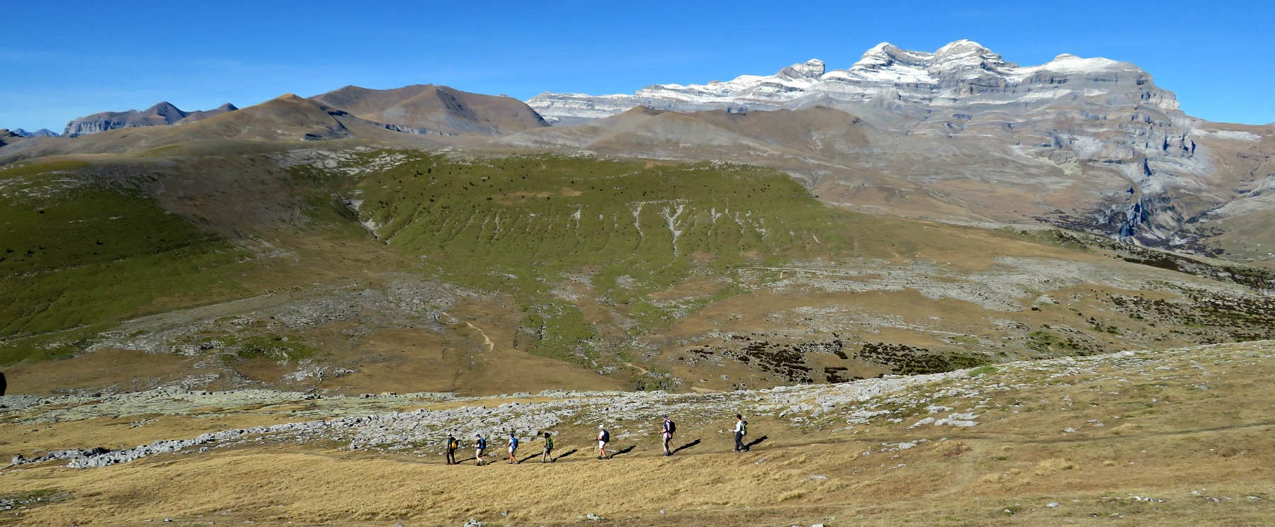 A group walking in the high Spanish Pyrenees with Monte Pedido inm view on Guided Walking Holiday Spain