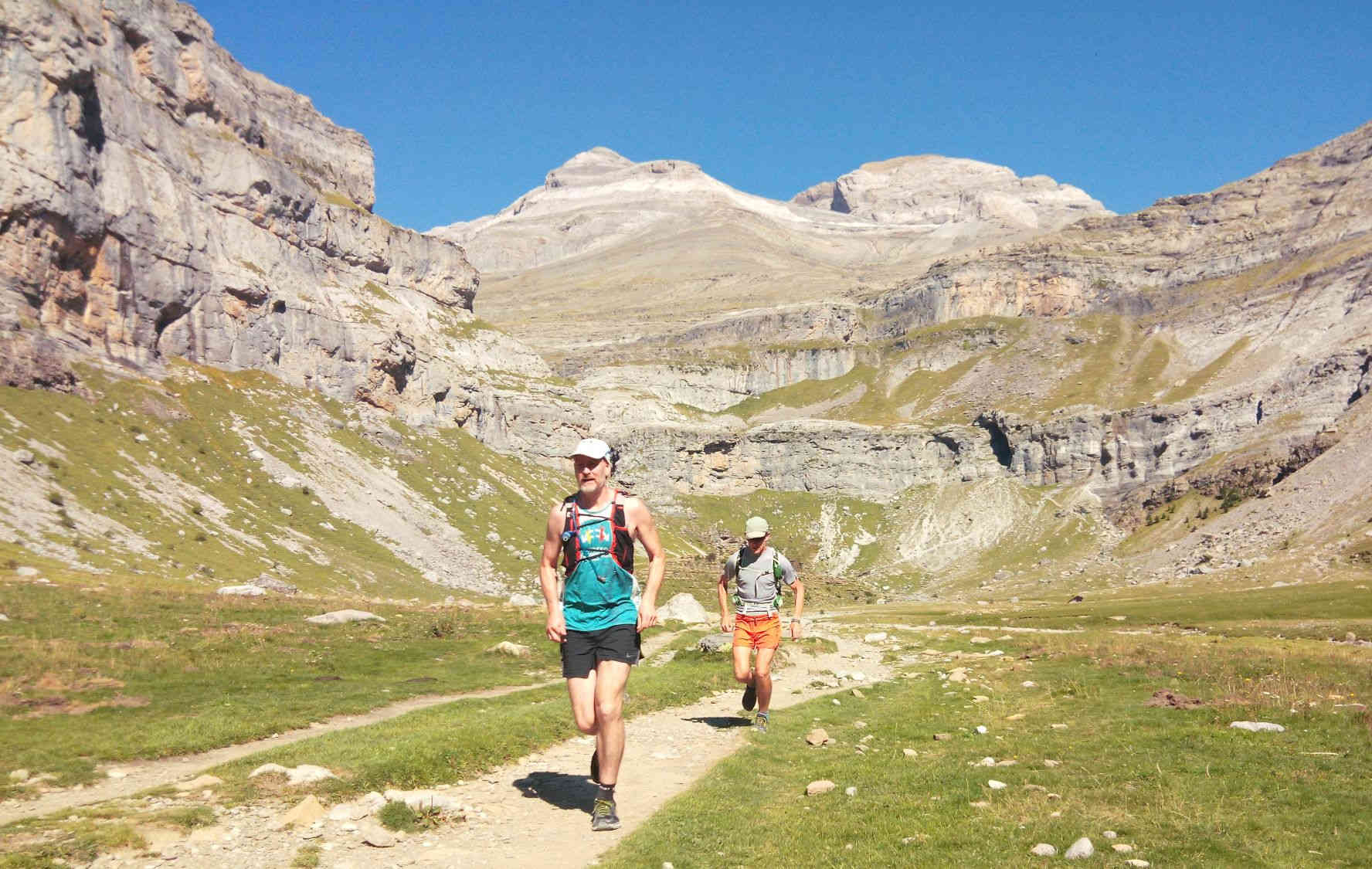 Two trail runners running on the track in the Ordesa valley with Monte Pedido behind on our Trail Running Holiday