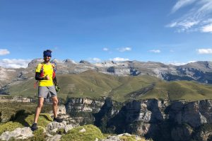 A trail runner on top of the world looking at the Añisclo canyon below on our Trail Running Holiday in the Spanish Pyrenees