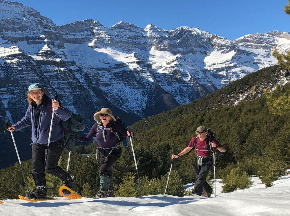 Walking on a ridge in the Spanish Pyrenees with snow covered mountains behind on our Snowshoeing Holidays Pyrenees