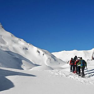 A group on snowshoes cross into France from Spain in beautiful sunshine on our Snowshoeing Holidays Pyrenees