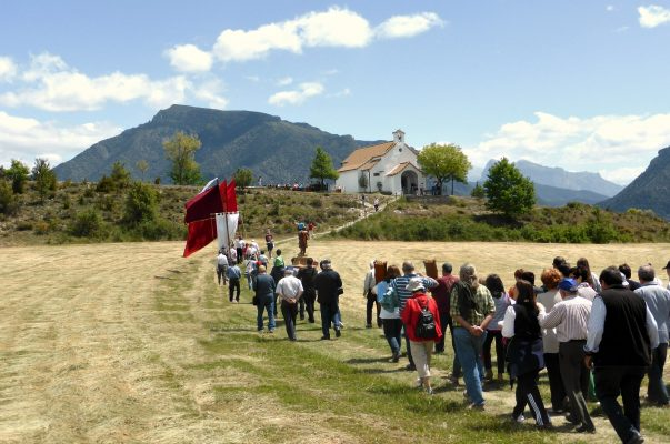 A procession of people with flags walk to the chapel of San Urbez for a service as part of the Albella village fiesta which get involved with on our Cultural Holiday spain