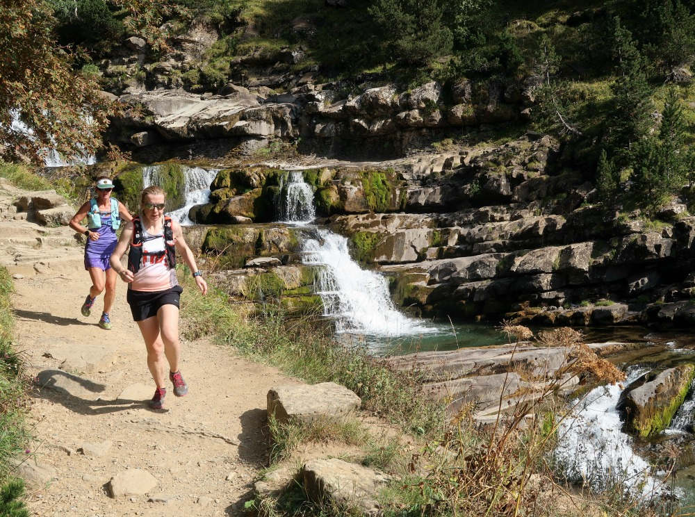 Two female trail ruuners in full stride by the grados de soaso as they descend from goriz on our Trail Running Holiday