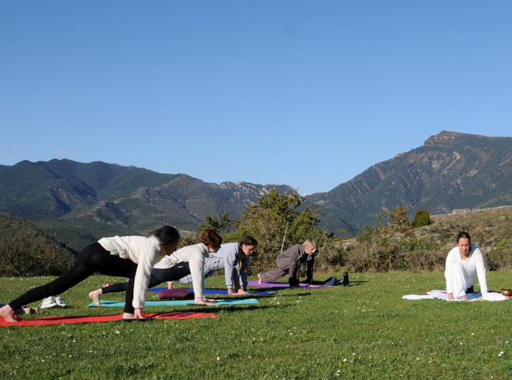 A group of yogis have a class outside with our teacher Tej with the Spanish Pyrenees providing the backdrop on our Yoga and Walking Retreat Spain