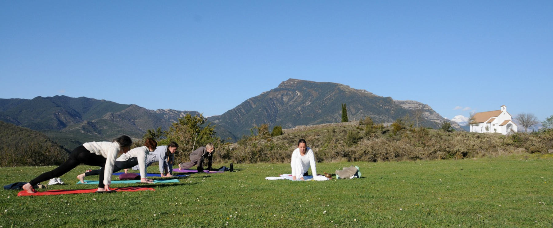 A group practice yoga outside by the small chapel of San Urbez in Albella in the Spanish Pyrenees on our Yoga and Walking Retreat Spain