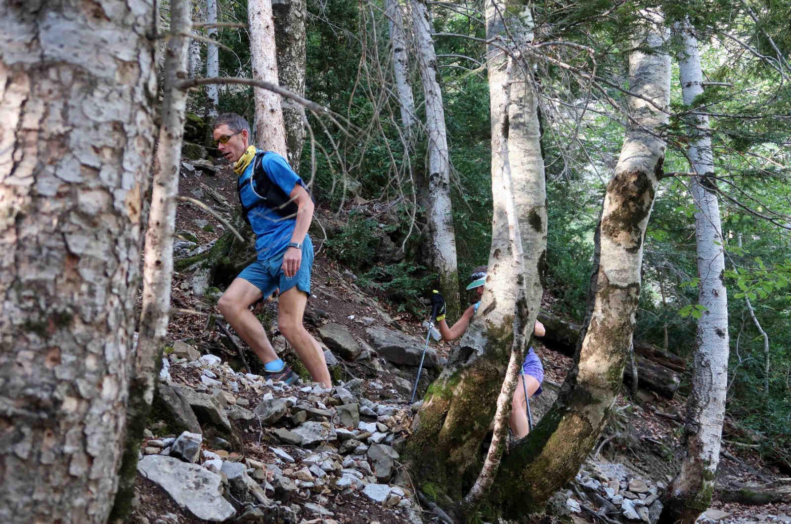 Trail running guide Jonathan runs up a wooded mountain path leading a group of trail runners in the Spanish Pyrenees on our Trail Running Holiday