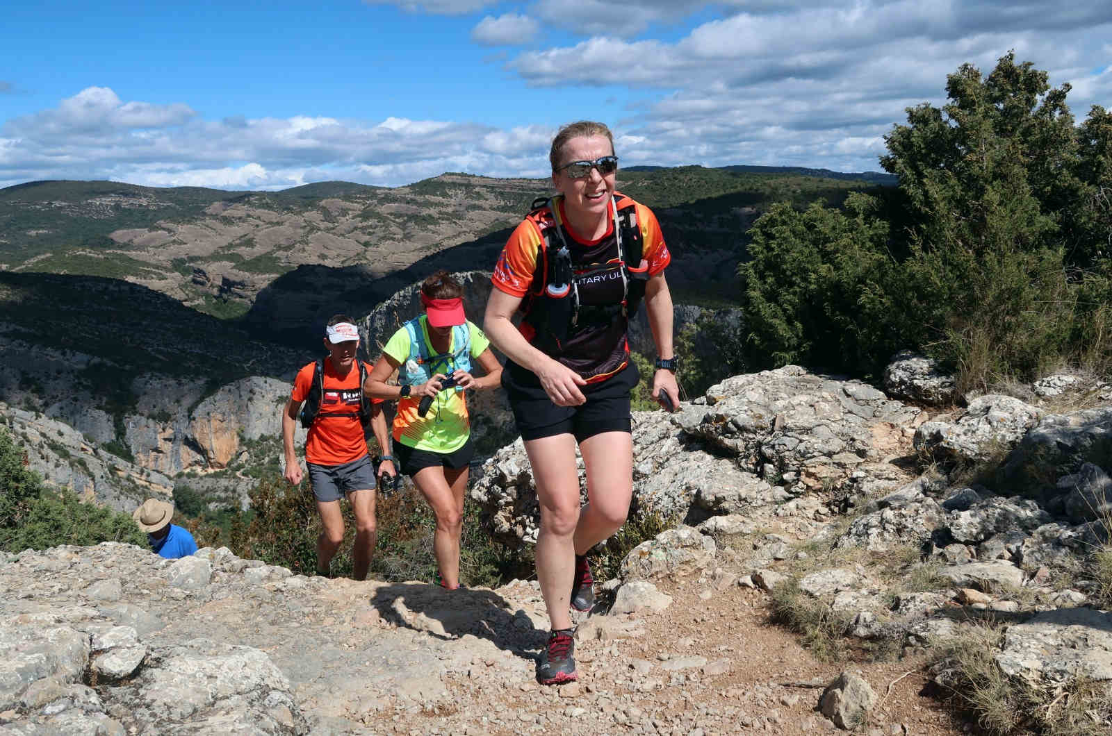 Four trail runners ascend a pathway emerging at the top of the plateau in the Spanish Pyrenees on our Trail Running Holiday
