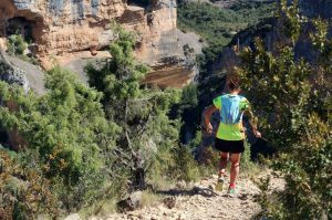 A female trail runner descends running on a gravel track into a gorge in the Spanish Pyrenees on our Trail Running Holiday