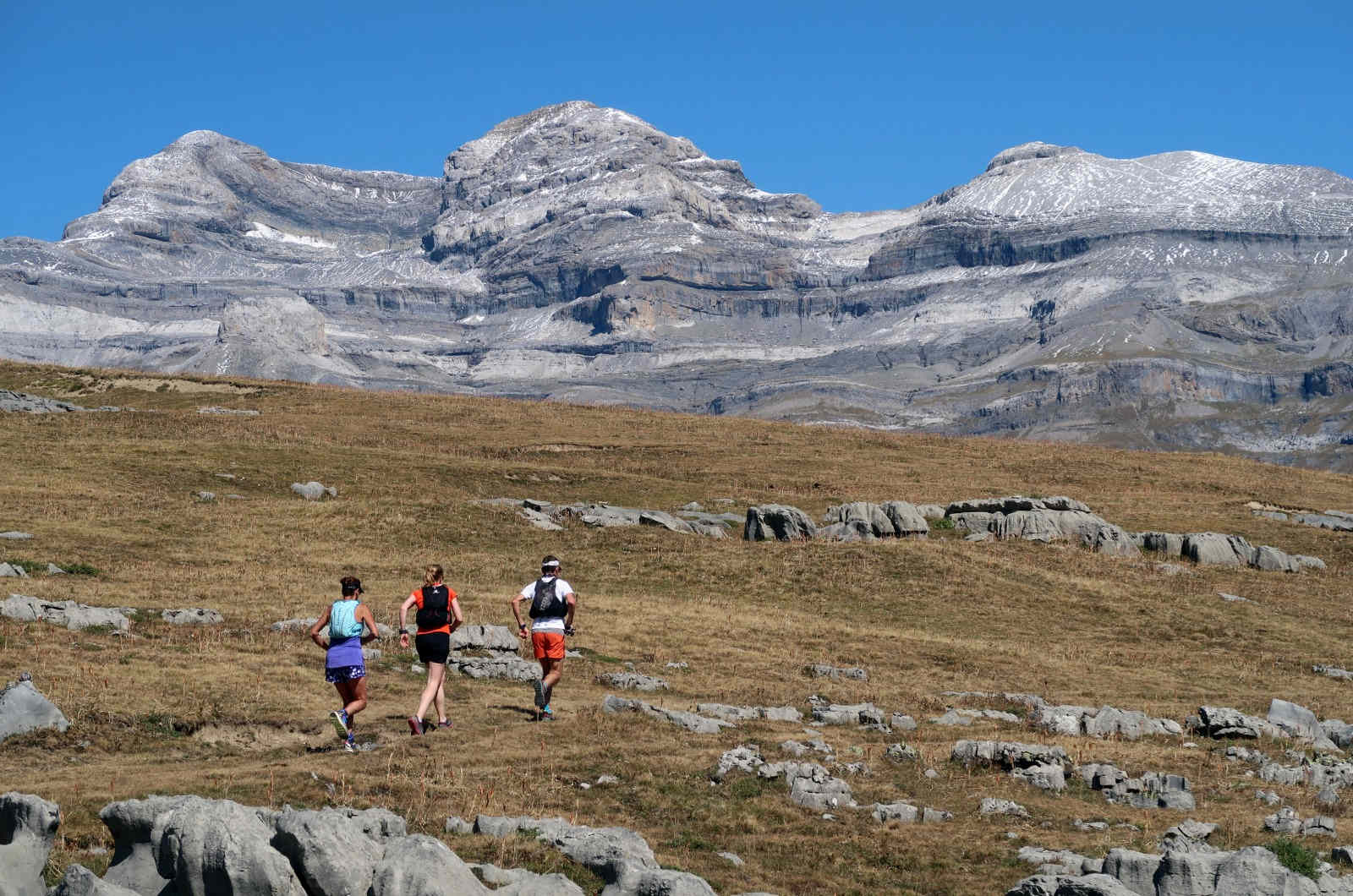 Three trail runners very high on a gradual ascent in the Spanish Pyrenees with Monte Pedido looming large behind them on our Trail Running Holiday