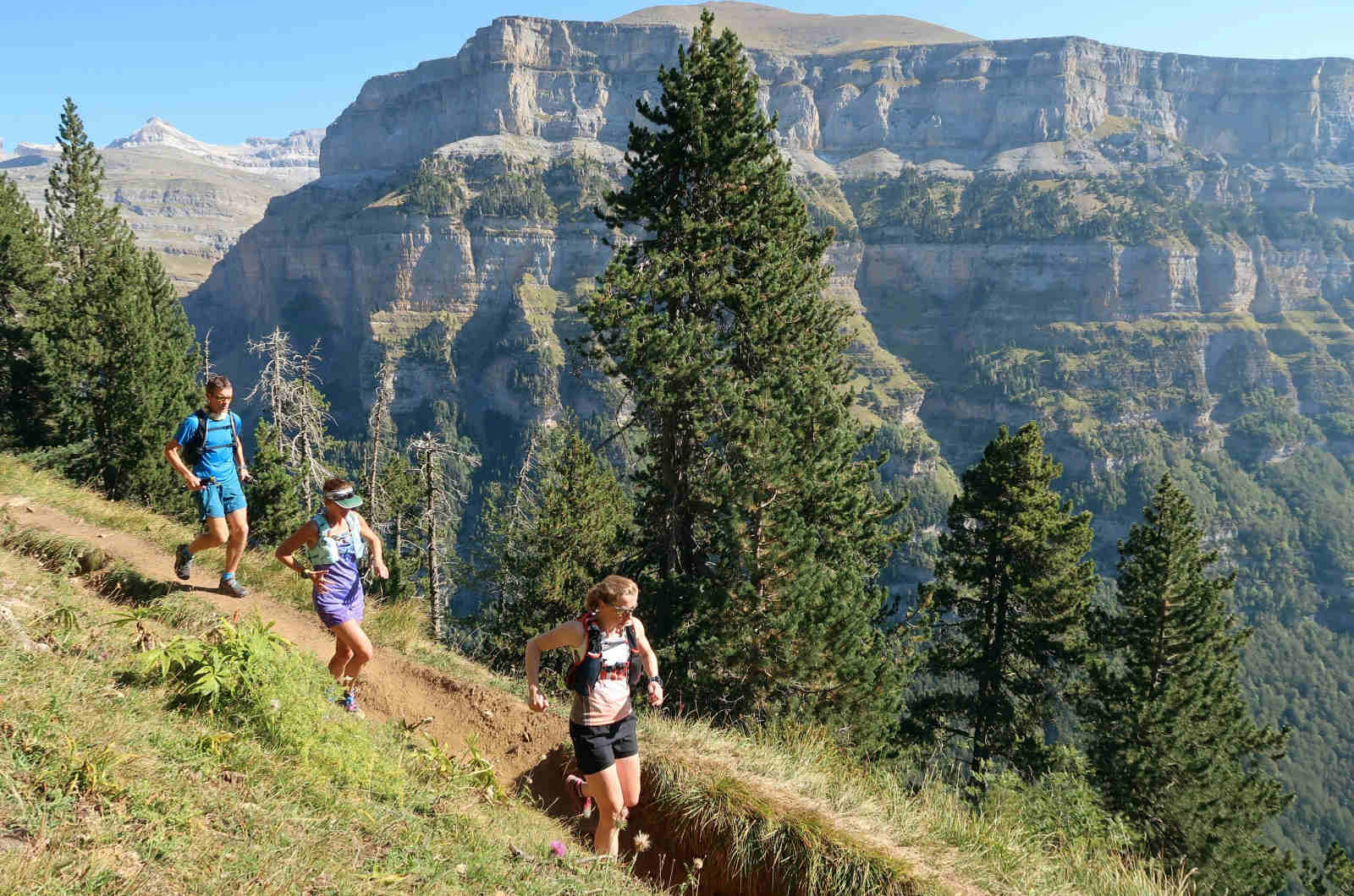Three trail runners running on single track in the Ordesa Natiional Park with stunning panoramic views on our Trail Running Holiday in the Spanish Pyrenees