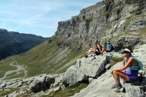 Three trail runners take a break to admire the stunning view of the Ordesa valley in the Spanish Pyrenees on our Trail Running Holiday