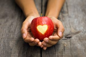 An apple cradled in a girls hands with a heart in the middle on Aragon Active Juice Retreat Spain