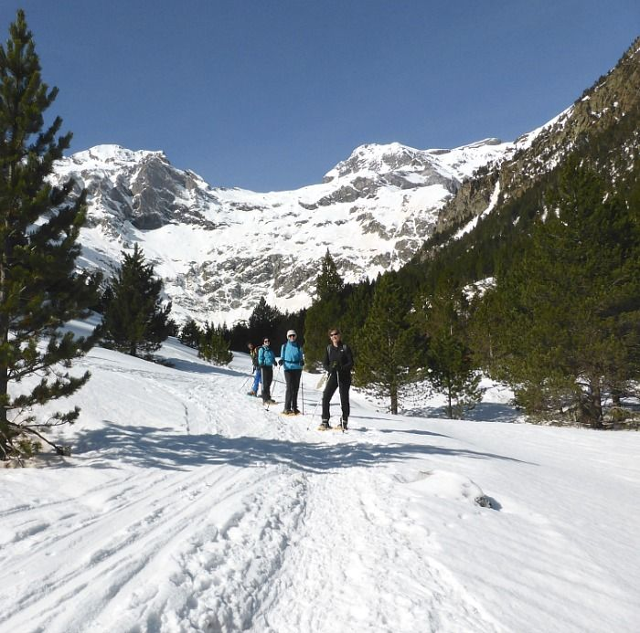 Snowshoeing in a forested valley in the Pyrenees with Aragon Active Snowshoeing down an open plain high in the Pyrenees on Aragon Active A group take a break at the summit of a mountain in the Pyrenees with Aragon Active Snowshoeing Holidays Pyrenees