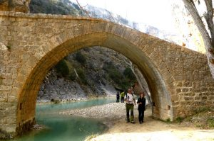 A couple walk under a medieval bridge in the Sierra de Guara on Snowshoeing Holidays Pyrenees with Aragon Active