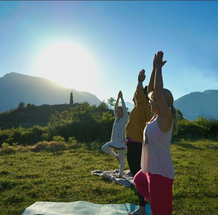 Morning yoga outside in the Pyrenees with the sun rising over the yogis shoulders on the Yoga Meditation Retreat Spain with Aragon Active