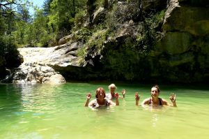 Three guests strike a meditation pose whilst wild swimming in the Pyrenees on Aragon Active Juice Retreat Spain