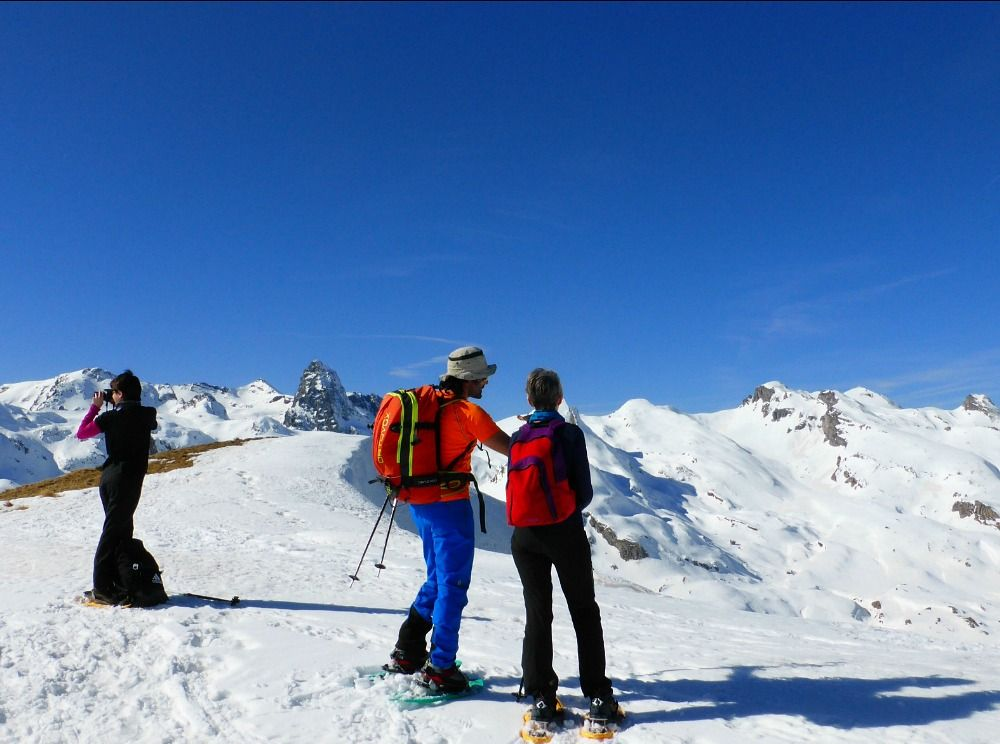 A group take a break at the summit of a mountain in the Pyrenees with Aragon Active Snowshoeing Holidays Pyrenees