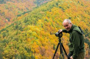 A photographer stands with camera ready to take the incredible autumn colours in the Pyrenees on the Photography Holiday Spain with Aragon Active